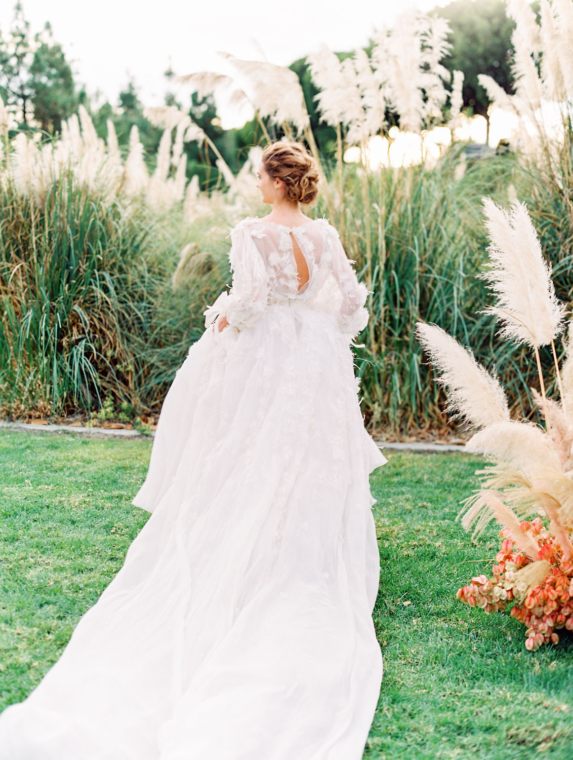 Bride in long sleeve Marchesa Poppy gown running through pampas grove, Pampas Grass Wedding in San Diego on Film by Cavin Elizabeth Photography