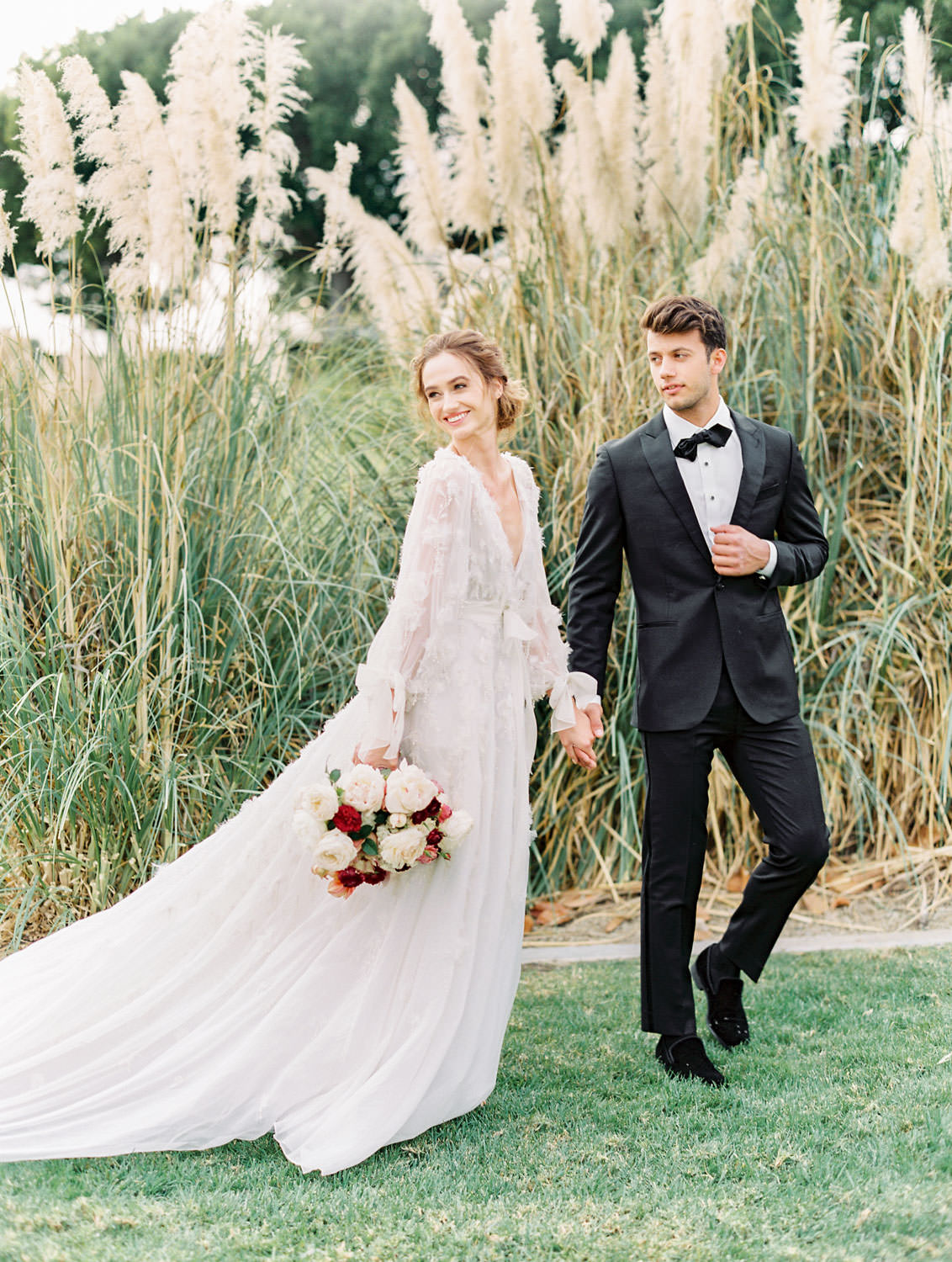 Bride in long sleeve Marchesa Poppy gown and groom in The Black Tux walking through pampas grove, Pampas Grass Wedding in San Diego on Film by Cavin Elizabeth Photography