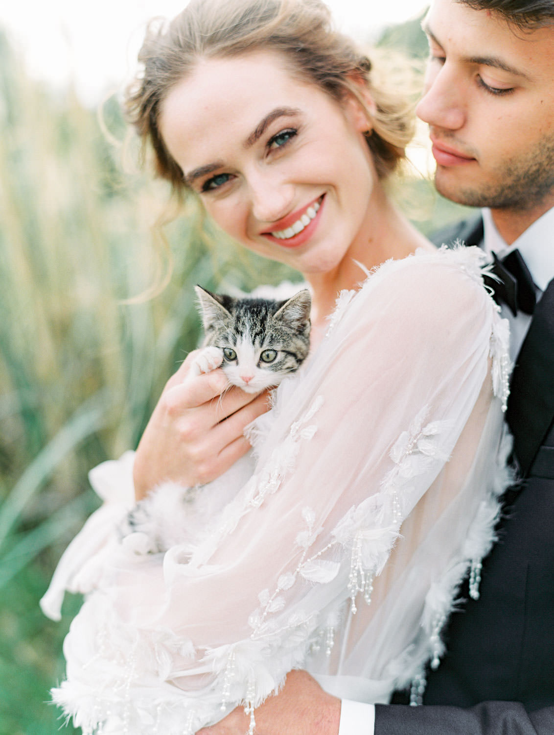 Bride in Marchesa Poppy gown and groom in The Black Tux holding a 7 week old kitten, Pampas Grass Wedding in San Diego on Film by Cavin Elizabeth Photography