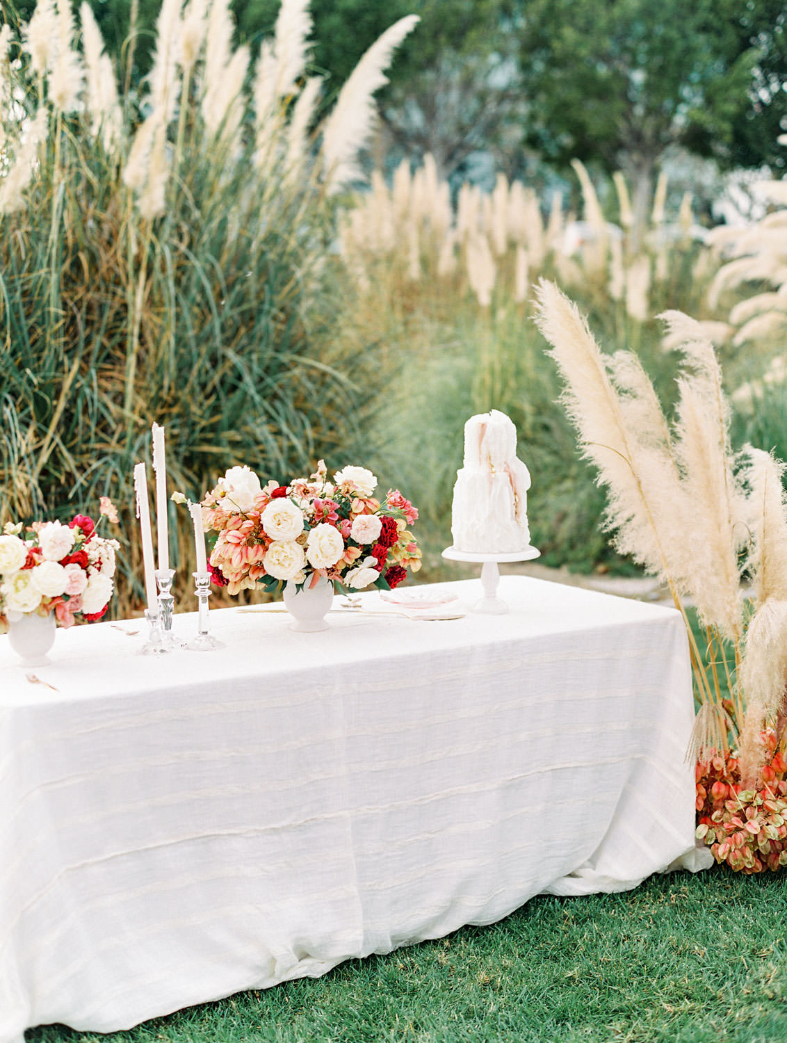 Cake table with flowers candles and cake, Textured white and blush two tier cake with accents of gold, Pampas Grass Wedding in San Diego on Film by Cavin Elizabeth Photography