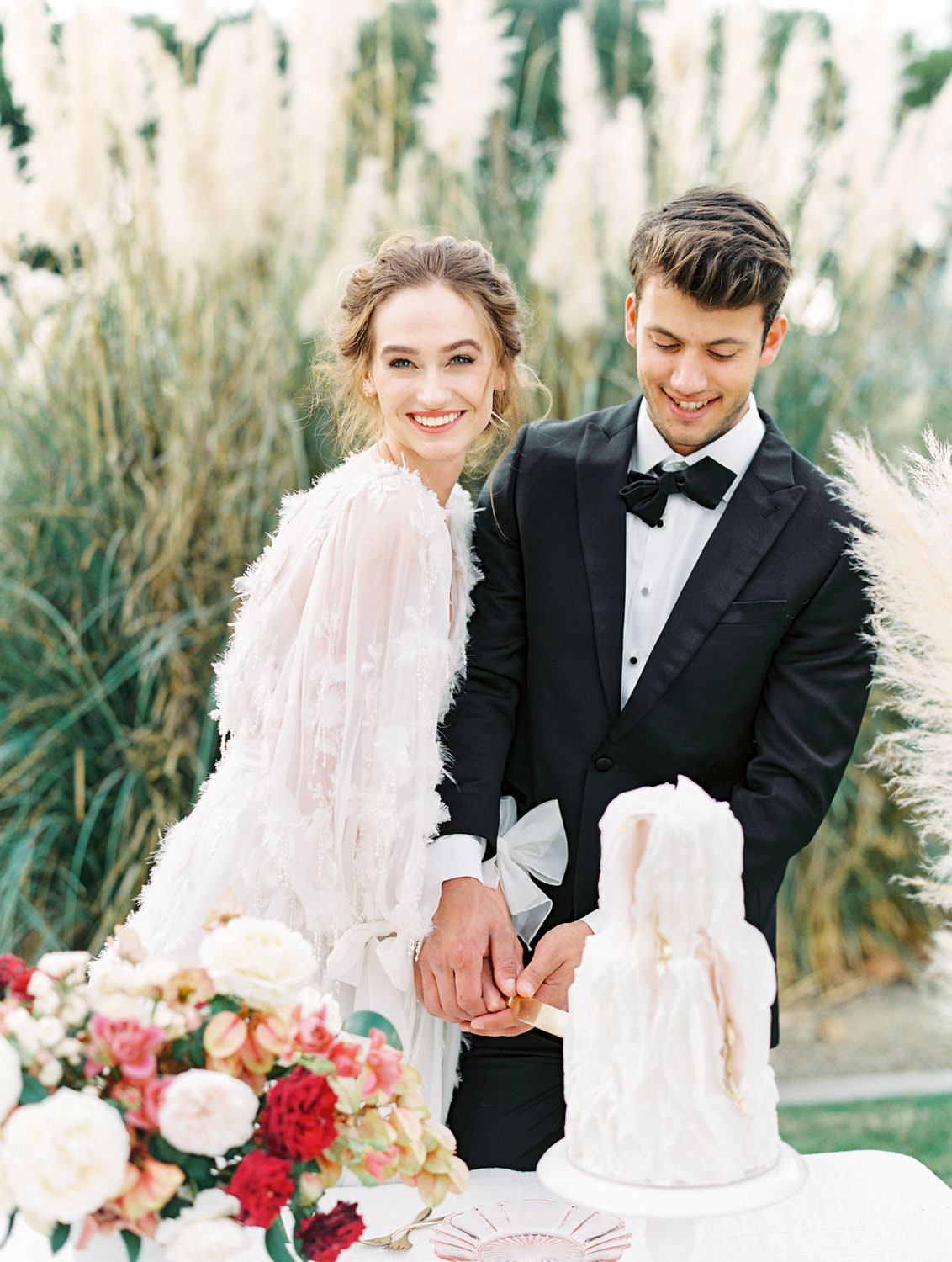 Bride in Marchesa Poppy gown and groom in The Black Tux cutting a textured white and blush two tier cake, Pampas Grass Wedding in San Diego on Film by Cavin Elizabeth Photography