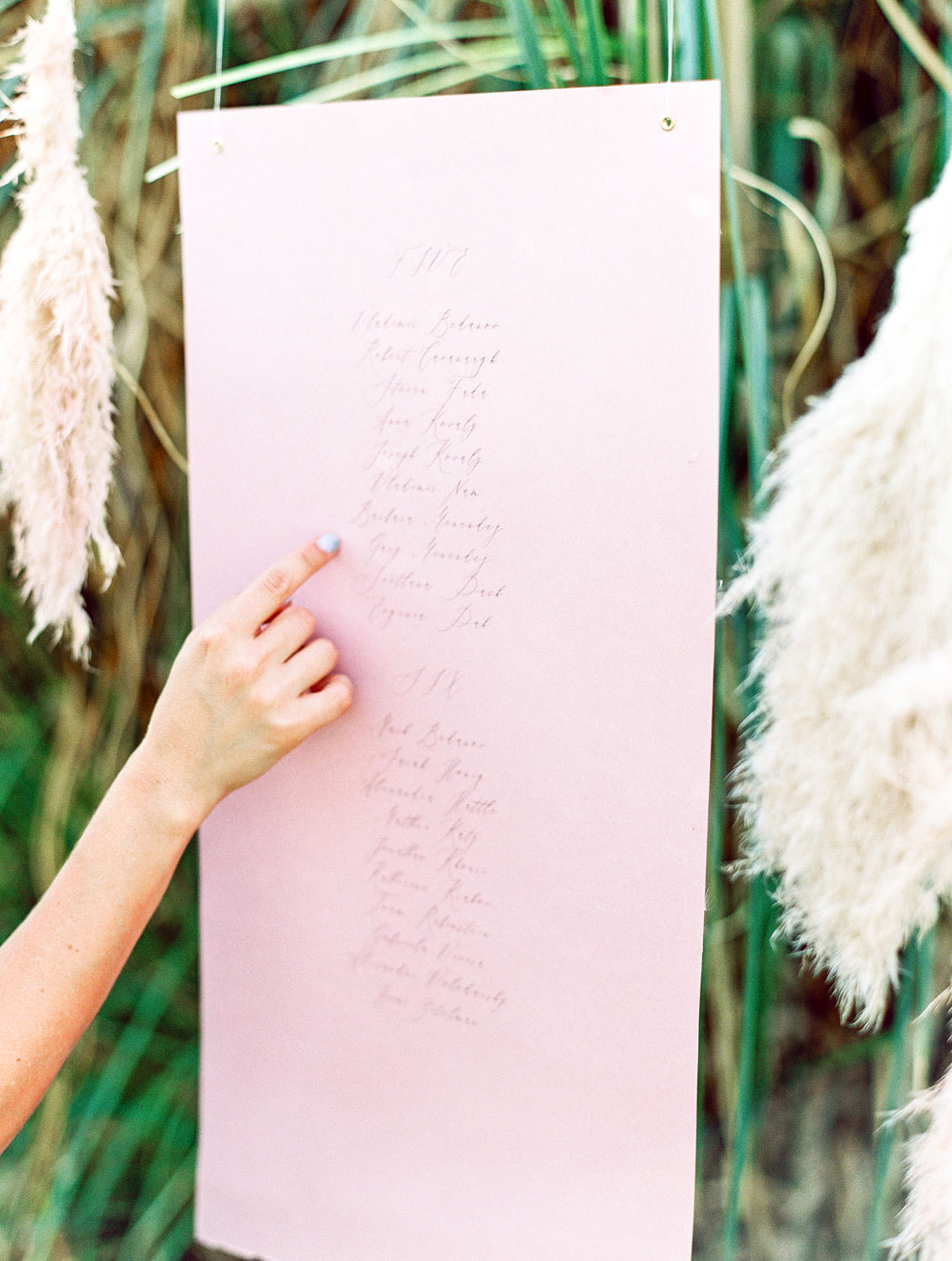 Hanging escort card display on pink paper with calligraphy, Pampas Grass Wedding in San Diego on Film by Cavin Elizabeth Photography