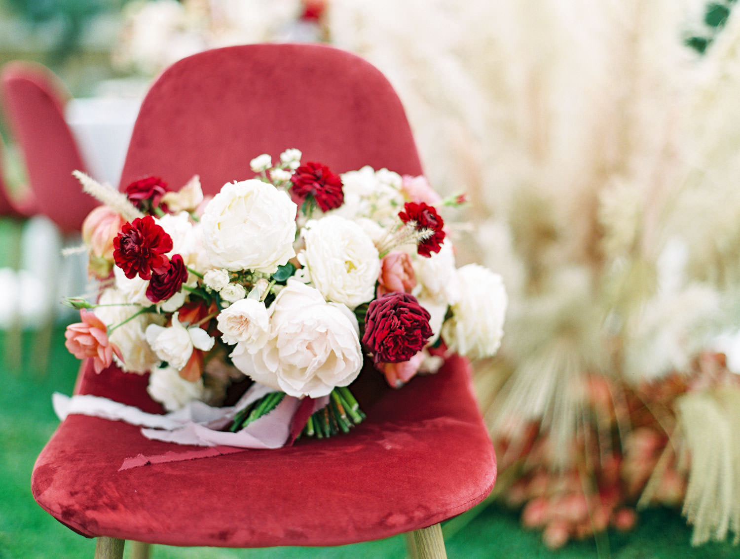 Burgundy velvet chair and bouquet with ivory blush red and neutral tones, Pampas Grass Wedding in San Diego on Film by Cavin Elizabeth Photography