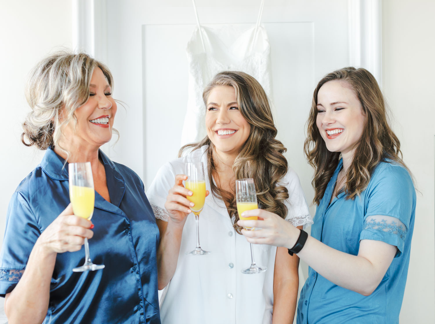 Bride with mother and maid of honor drinking mimosas in robes laughing, Intimate Wedding at La Valencia Hotel in La Jolla by Cavin Elizabeth Photography