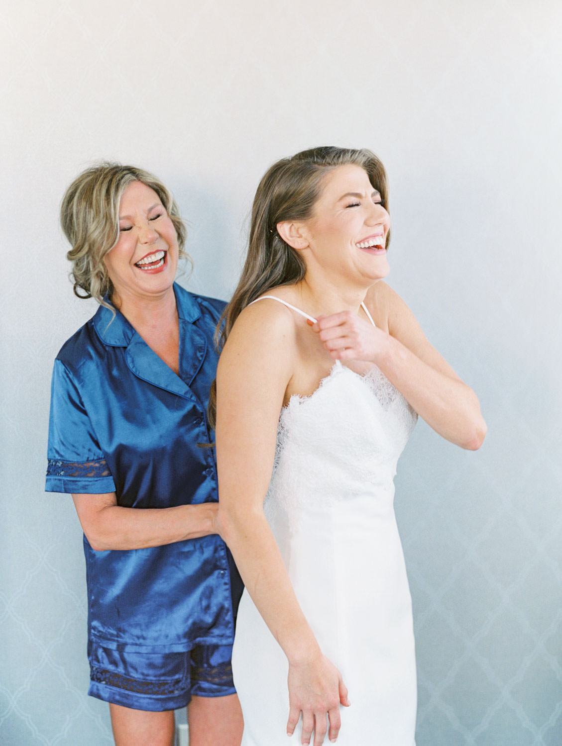 Mother of the bride in a blue pajama set helping bride into her gown laughing, Intimate Wedding at La Valencia Hotel in La Jolla by film photographer Cavin Elizabeth Photography