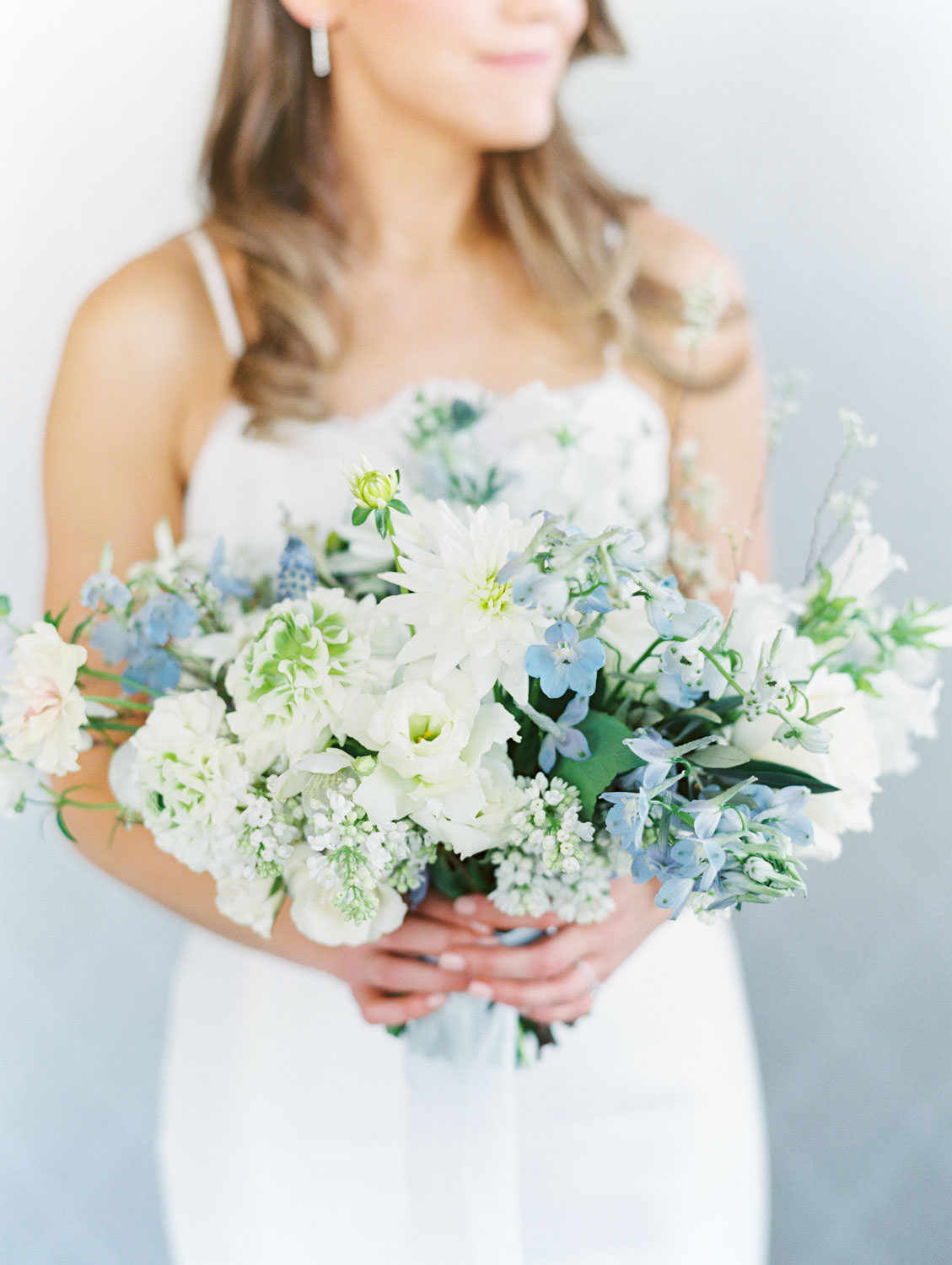 Glamorous and chic bride holding a bridal bouquet made with ivory, blue, and green flowers on film, Intimate Wedding at La Valencia Hotel in La Jolla by Cavin Elizabeth Photography