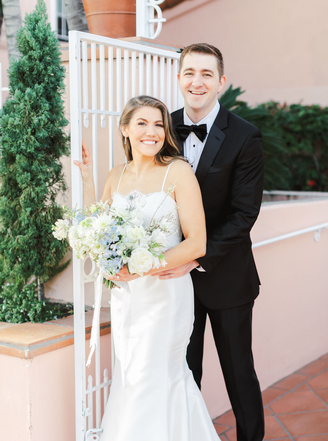 Bride and groom portrait by white gate and pink walls, Intimate Wedding at La Valencia Hotel in La Jolla by Cavin Elizabeth Photography