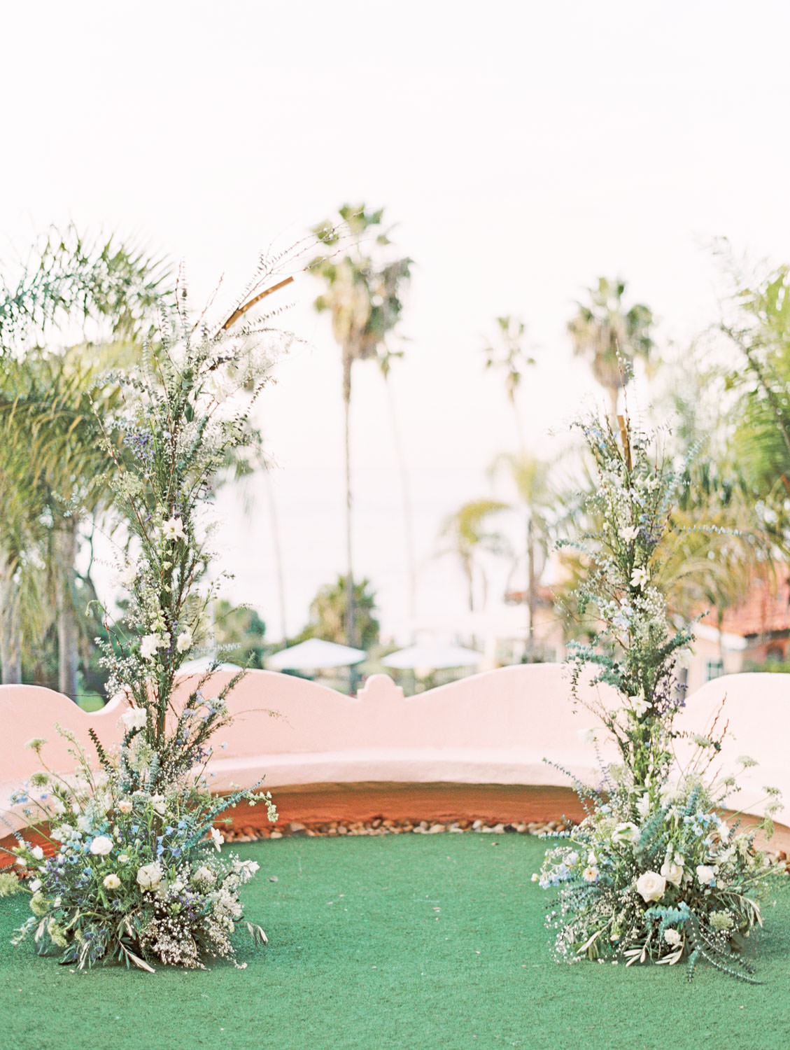 Wedding ceremony on lawn surrounded by pink benches and ocean view, ceremony arch with organic green, ivory, and blue tall floral arrangements, Intimate Wedding at La Valencia Hotel in La Jolla by Cavin Elizabeth Photography