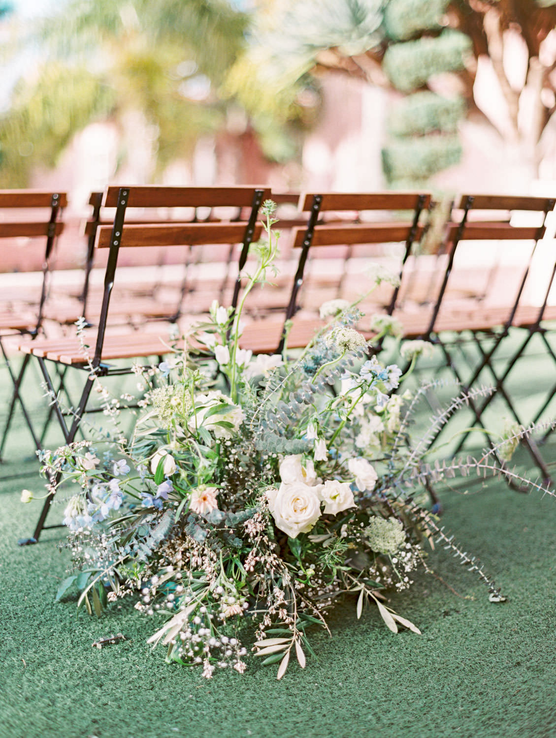 Wedding ceremony on lawn with bistro chairs and organic green, ivory, and blue tall floral arrangements, Intimate Wedding at La Valencia Hotel in La Jolla by Cavin Elizabeth Photography