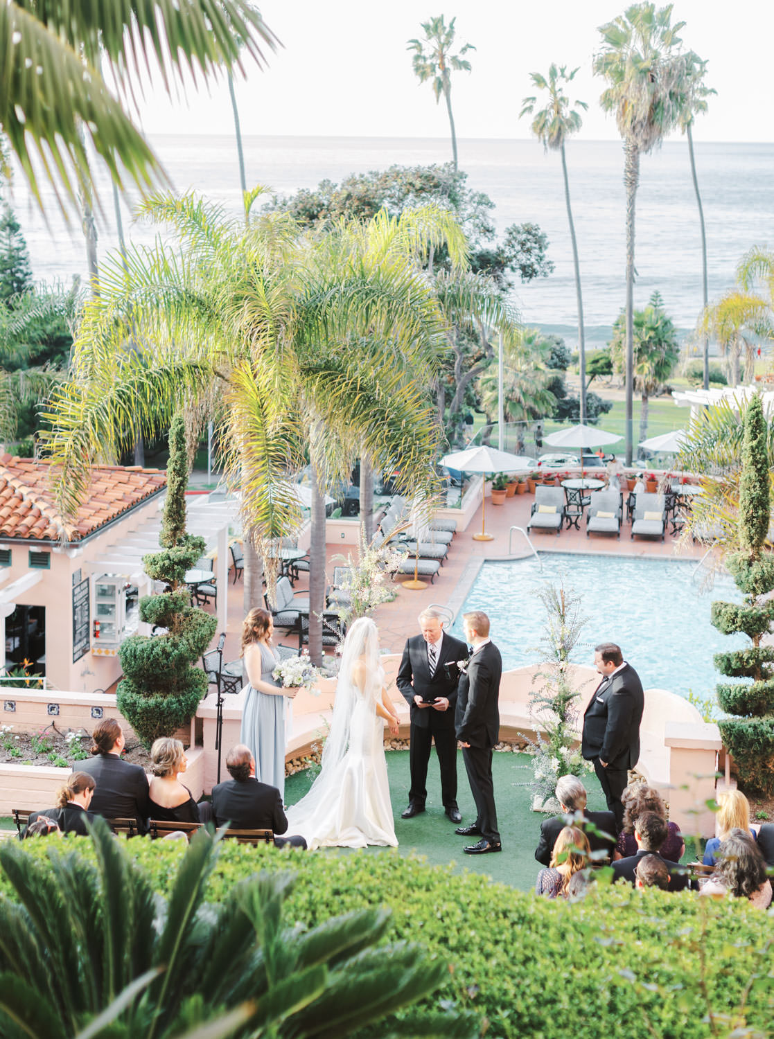 Breaktaking ocean and palm tree views overlooking a pool and surrounded by green hedges for a stunning wedding ceremony, Intimate Wedding at La Valencia Hotel in La Jolla by Cavin Elizabeth Photography