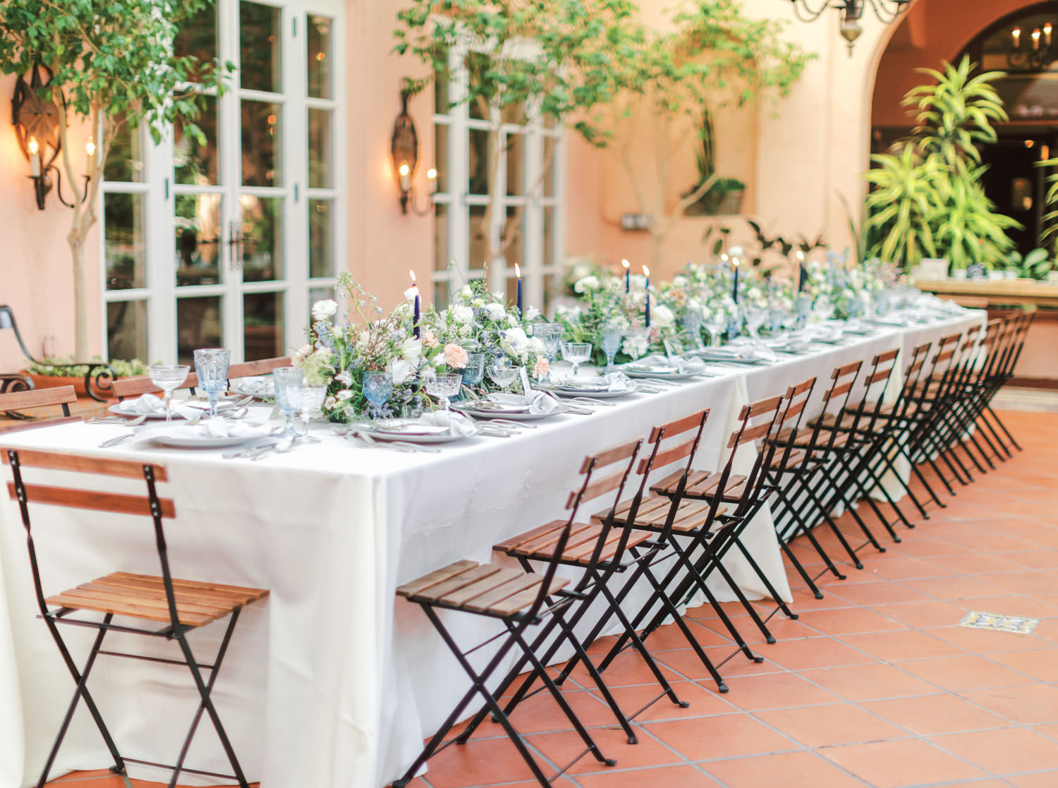 One long table for 26 guests with ivory linen, bistro chairs, green, peach, and ivory floral arrangements, navy taper candles, grey dinnerware, and blue and crystal glassware. Intimate Wedding at La Valencia Hotel in La Jolla by Cavin Elizabeth Photography