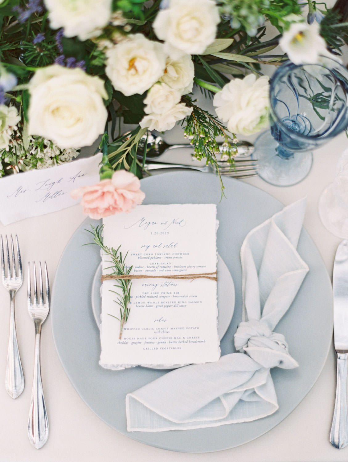 Place setting with ivory linen, green, peach, and ivory floral arrangements, navy taper candles, grey dinnerware, and blue and crystal glassware. White hand torn menu with navy calligraphy. Intimate Wedding at La Valencia Hotel in La Jolla by Cavin Elizabeth Photography