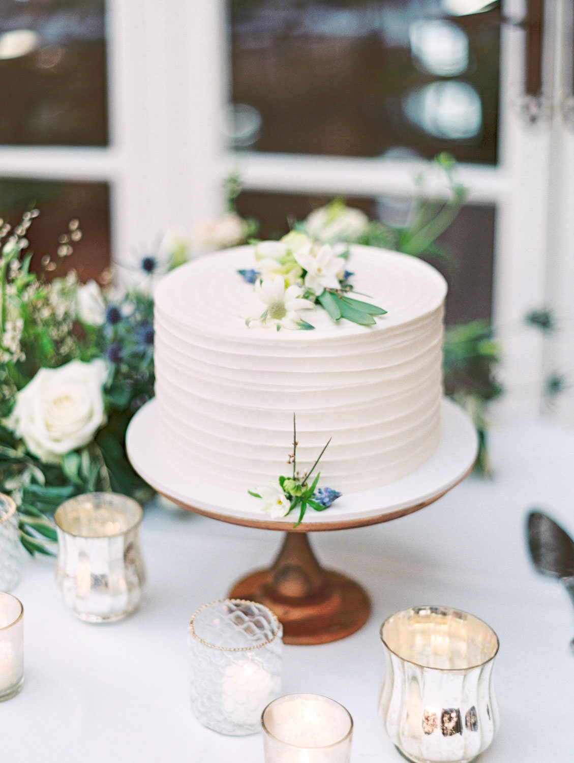 White one tier cake with ivory linen, green, peach, and ivory floral arrangements and mixed glass and metal votives. Intimate Wedding at La Valencia Hotel in La Jolla by Cavin Elizabeth Photography
