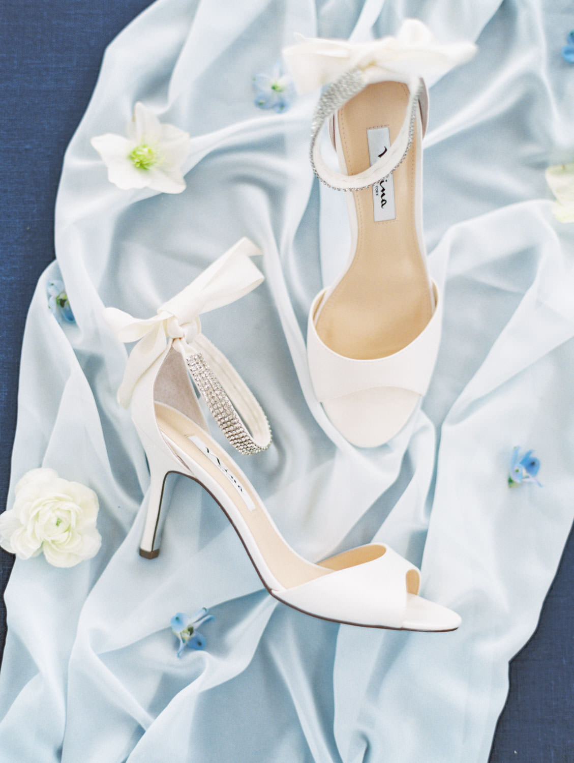 Ivory peep toe silk wedding heels with bow tied at the back shot on film on a navy styling board, Intimate Wedding at La Valencia Hotel in La Jolla by Cavin Elizabeth Photography