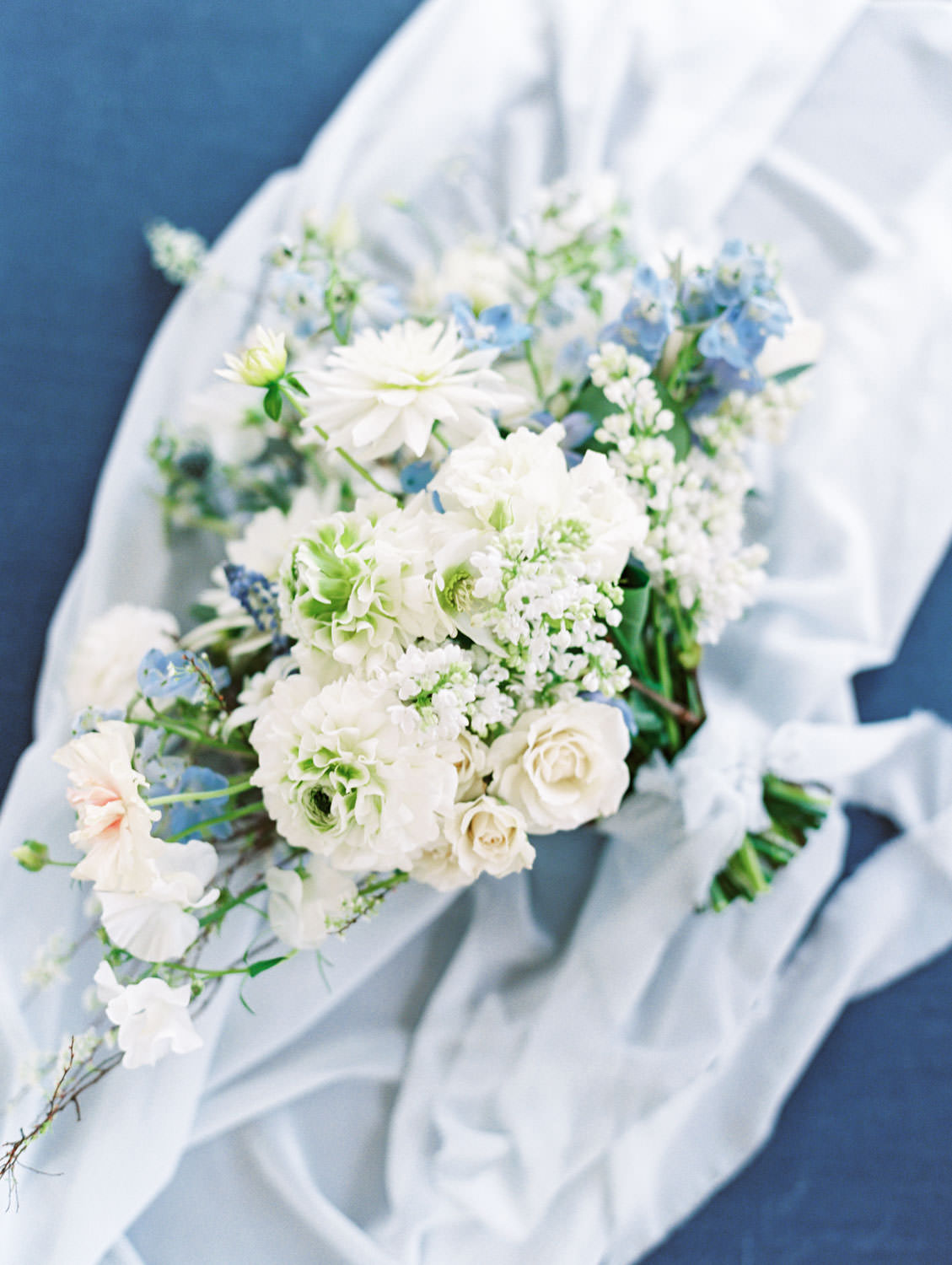 Ivory, green, soft peach, and blue bridal bouquet shot on film on a navy styling board, Intimate Wedding at La Valencia Hotel in La Jolla by Cavin Elizabeth Photography