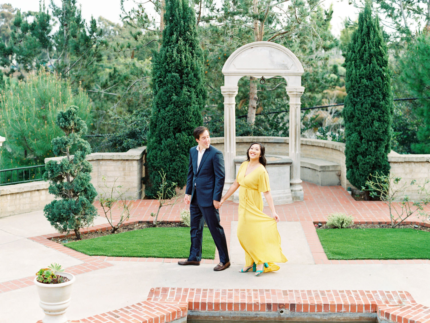 Bride in yellow flowy dress and groom in navy suit, The Prado wishing well engagement film photos by Cavin Elizabeth Photography