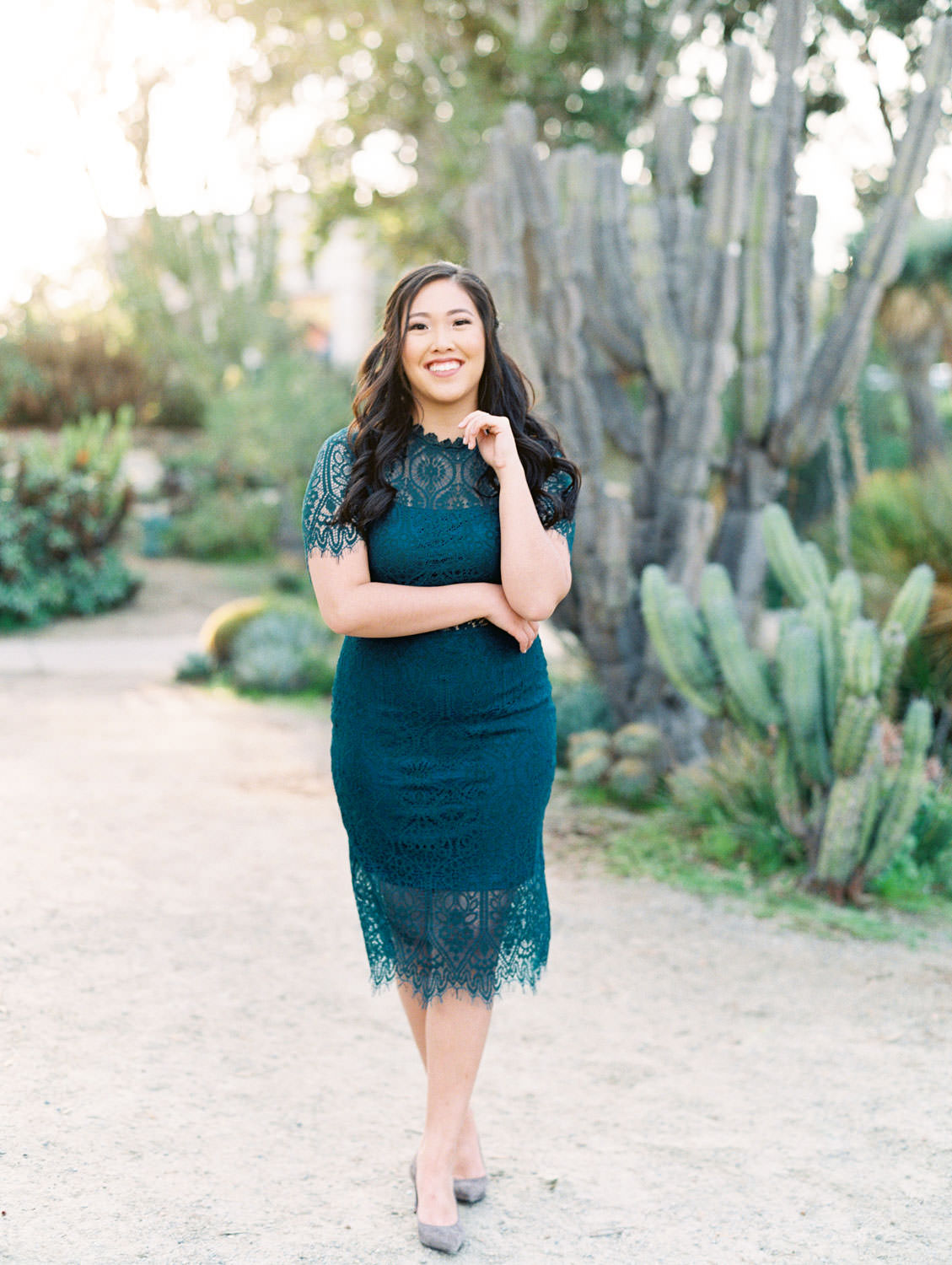 Bride wearing dark teal lace cut dress with curled hair and soft makeup with grey pumps, Balboa Park cactus garden engagement film photos by Cavin Elizabeth Photography