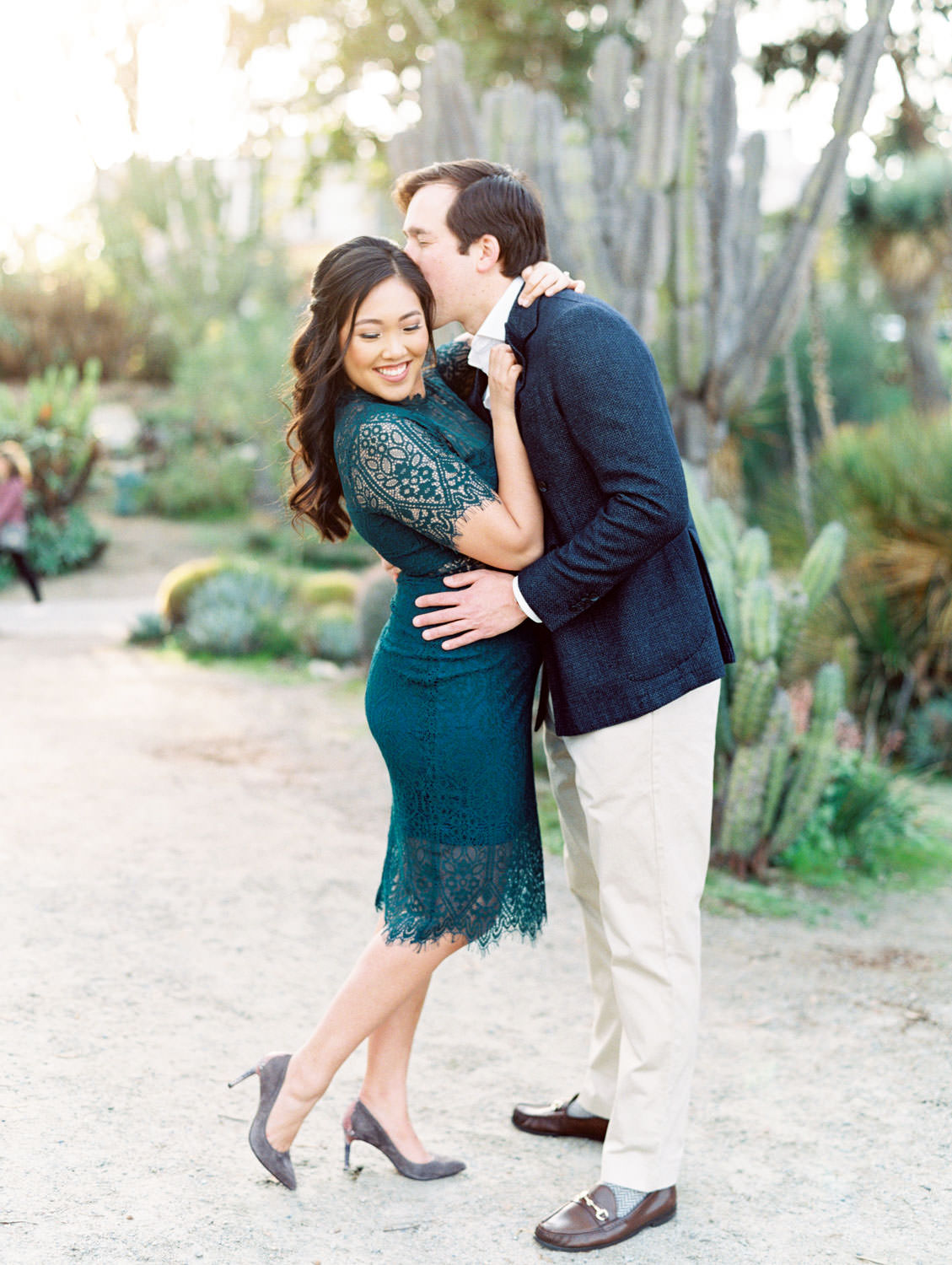 Bride wearing dark teal lace cut dress with curled hair and soft makeup being kissed by Groom in navy wool suit jacket and khakis, Balboa Park cactus garden engagement film photos by Cavin Elizabeth Photography