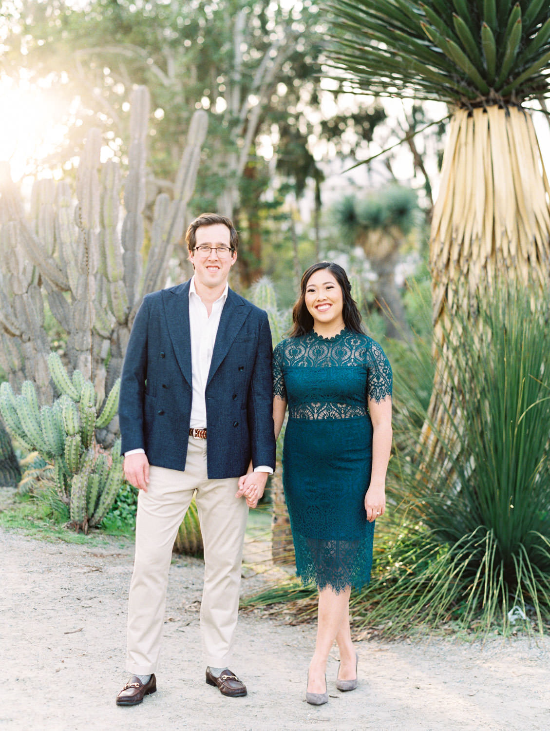 Bride wearing dark teal lace cut dress with curled hair. Groom in navy wool suit jacket and khakis, Balboa Park cactus garden engagement film photos by Cavin Elizabeth Photography