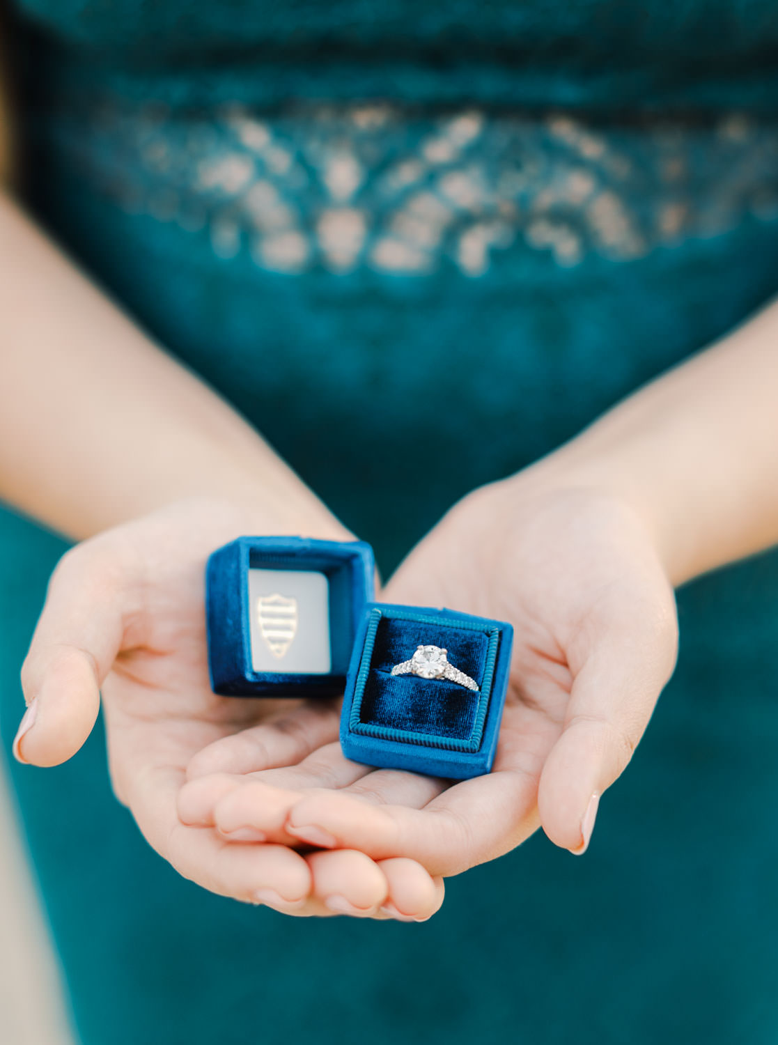 Bride wearing dark teal lace cut dress holding her engagement ring in a navy blue Mrs Box, Balboa Park cactus garden engagement photos by Cavin Elizabeth Photography