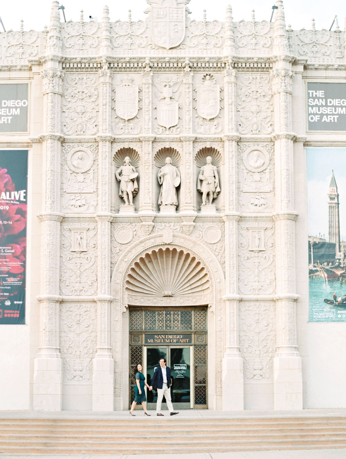 Wide architectural photo of bride wearing dark teal lace cut dress with curled hair and soft makeup walking with Groom in navy wool suit jacket and khakis, Balboa Park San Diego Museum of Art engagement film photos by Cavin Elizabeth Photography