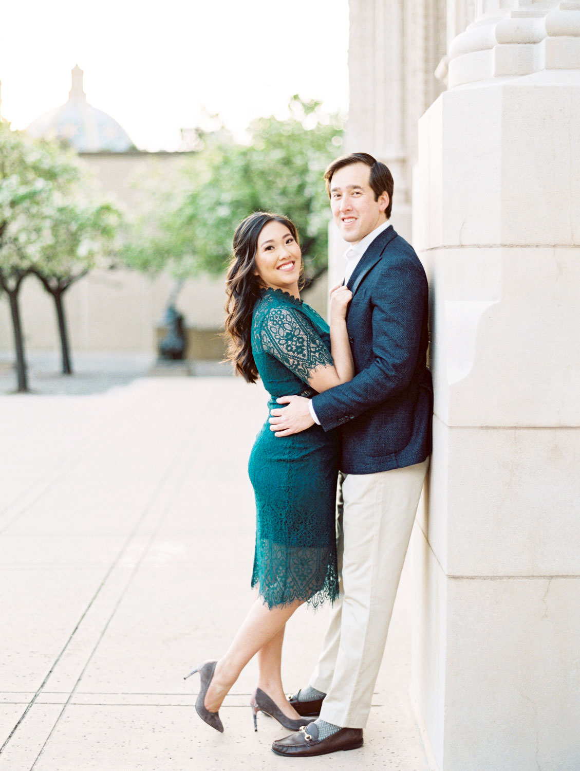 Bride wearing dark teal lace cut dress with curled hair and soft makeup snuggled up with Groom in navy wool suit jacket and khakis, Balboa Park San Diego Museum of Art engagement film photos by Cavin Elizabeth Photography