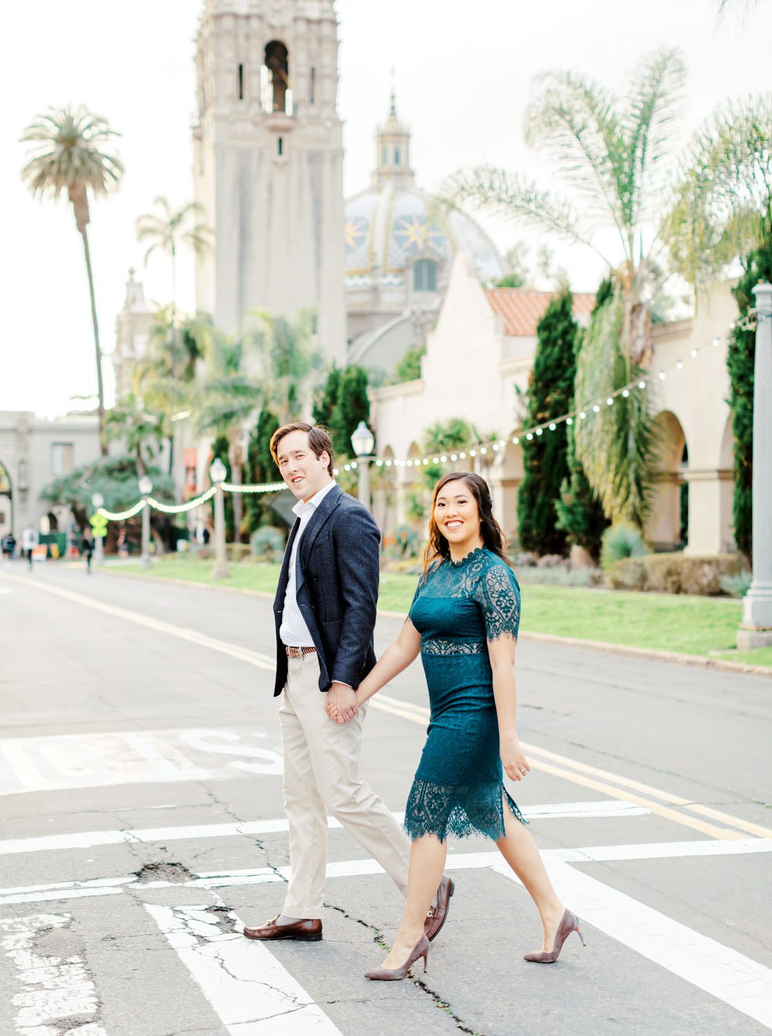 Bride wearing dark teal lace cut dress with curled hair and soft makeup walking Groom in navy wool suit jacket and khakis, Balboa Park bell tower engagement photos by Cavin Elizabeth Photography