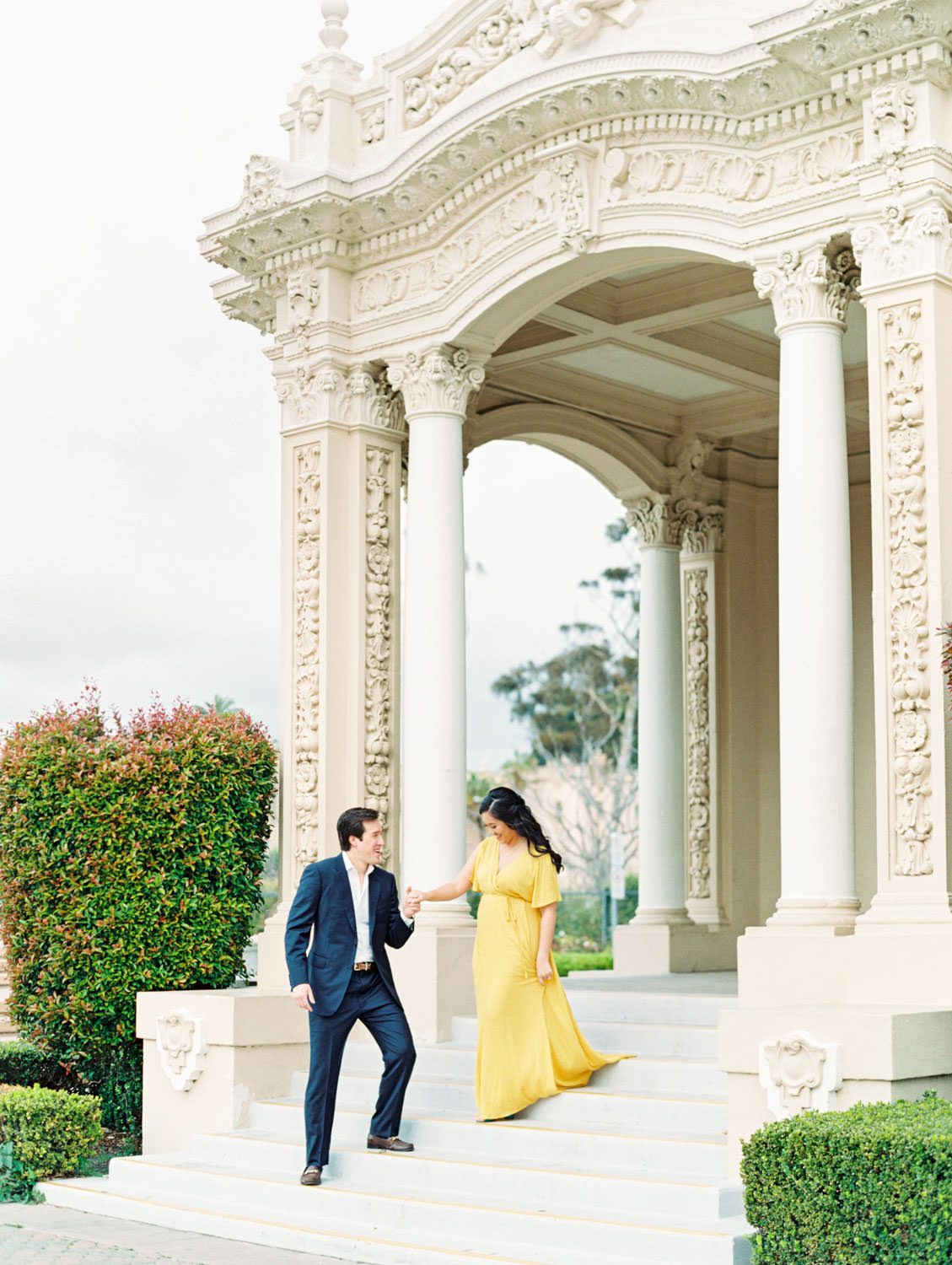 Bride in yellow flowy dress and groom in navy suit walking down stairs, Film Balboa Park Organ Pavilion Engagement Photos by Cavin Elizabeth Photography