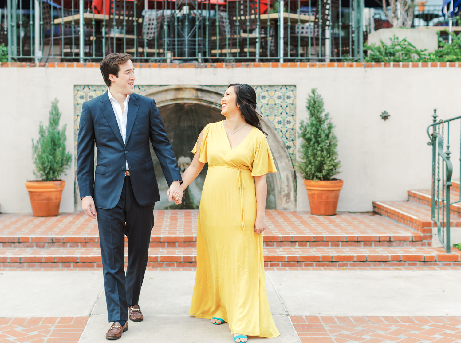 Bride in yellow flowy dress and groom in navy suit, The Prado engagement wishing well photos by Cavin Elizabeth Photography