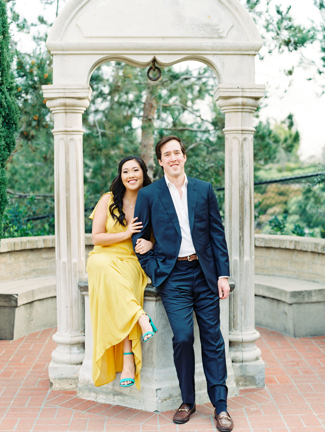 Bride in yellow flowy dress and groom in navy suit sitting on fountain, The Prado wishing well engagement film photos by Cavin Elizabeth Photography