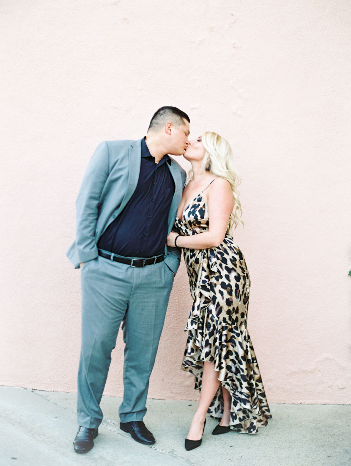 Bride in a leopard print dress and groom in grey suit kissing in front of a pink wall, film Beverly Hills Hotel Engagement Photos by Cavin Elizabeth Photography