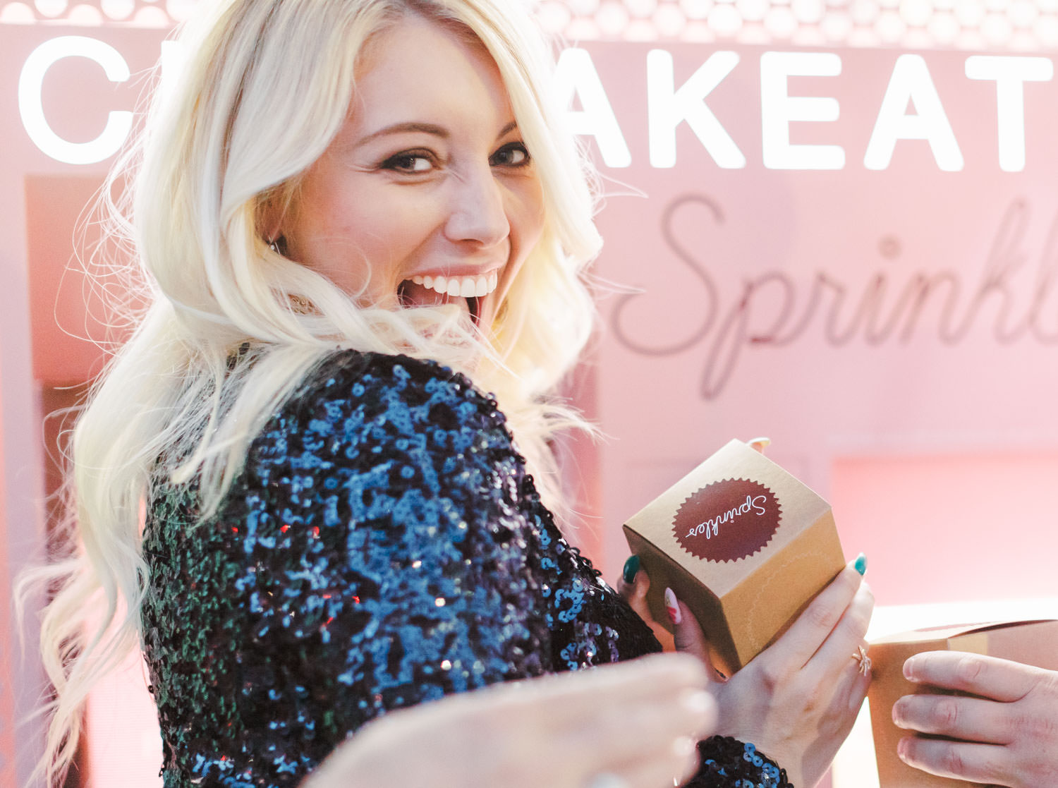 Bride getting cupcake at Sprinkles ATM wearing a black sequin dress, Beverly Hills Sprinkles Cupcake Engagement Photos by Cavin Elizabeth Photography