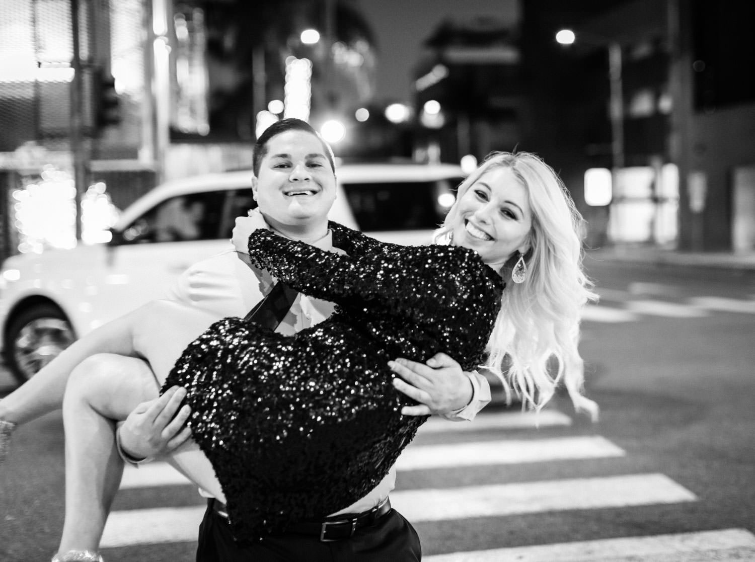 Groom carrying bride across the street at night, Beverly Hills downtown Engagement Photos by Cavin Elizabeth Photography