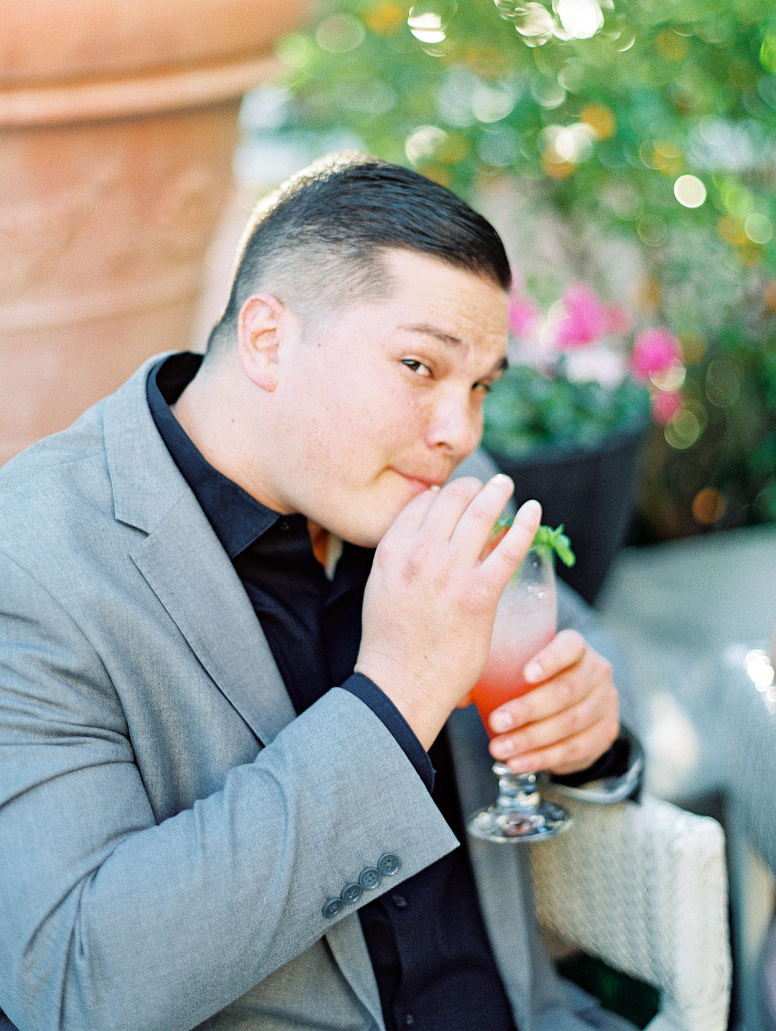 Groom in grey suit sipping cocktails on a patio, film Beverly Hills Hotel Engagement Photos by Cavin Elizabeth Photography
