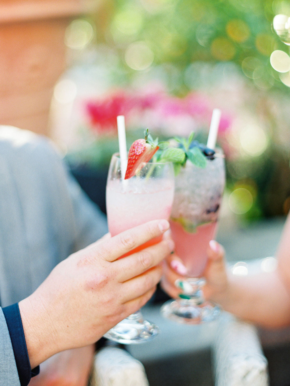 Cheersing strawberry and blueberry cocktails on a patio, film Beverly Hills Hotel Engagement Photos by Cavin Elizabeth Photography