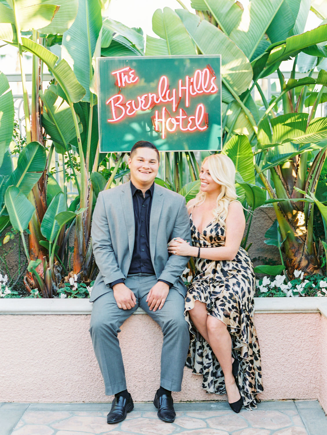 Bride in a leopard print dress and groom in grey suit sitting below the Beverly Hills Hotel neon sign, film Beverly Hills Hotel Engagement Photos by Cavin Elizabeth Photography