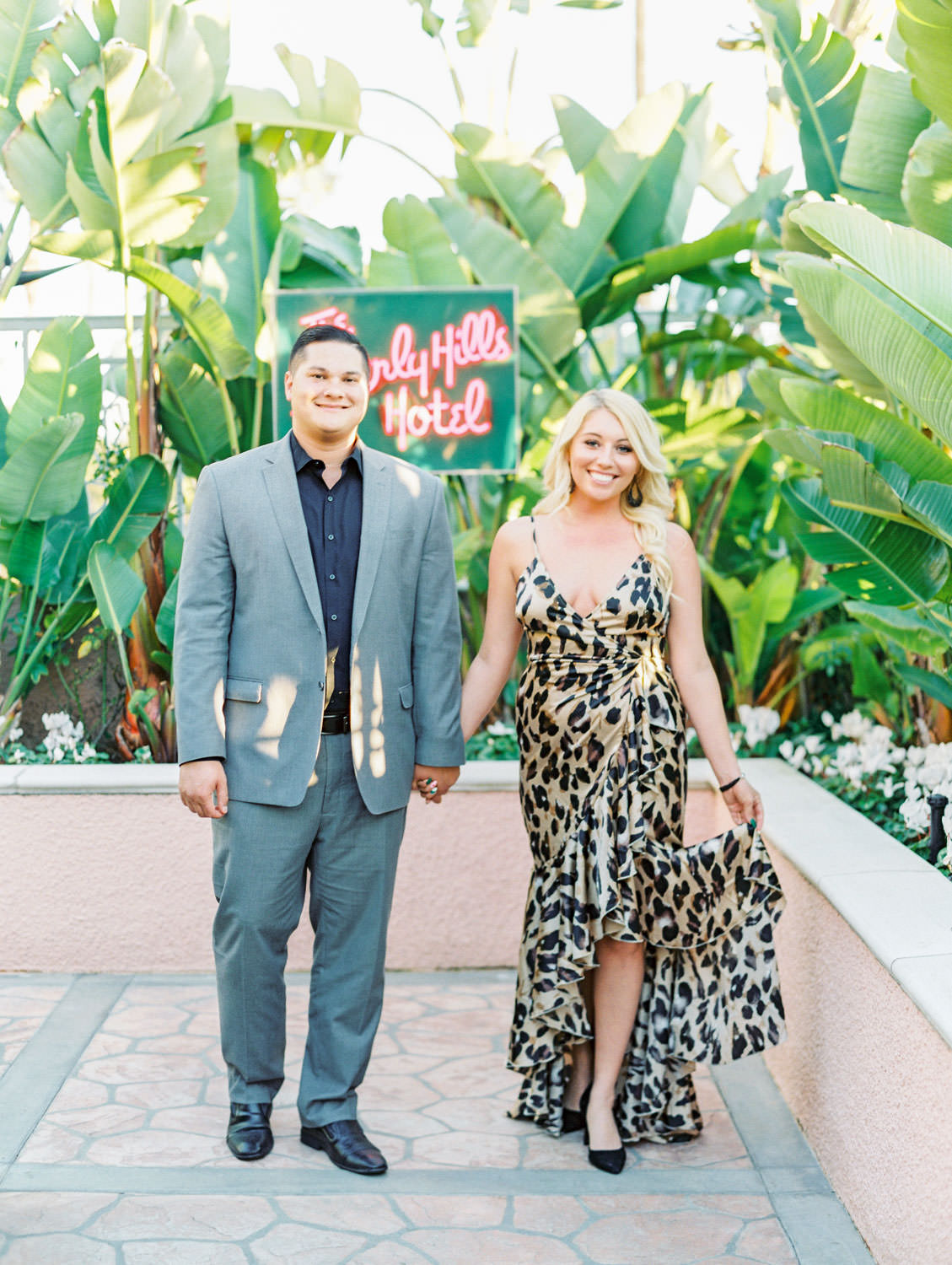Bride in a leopard print dress and groom in grey suit walking in front of the Beverly Hills Hotel neon sign, film Beverly Hills Hotel Engagement Photos by Cavin Elizabeth Photography