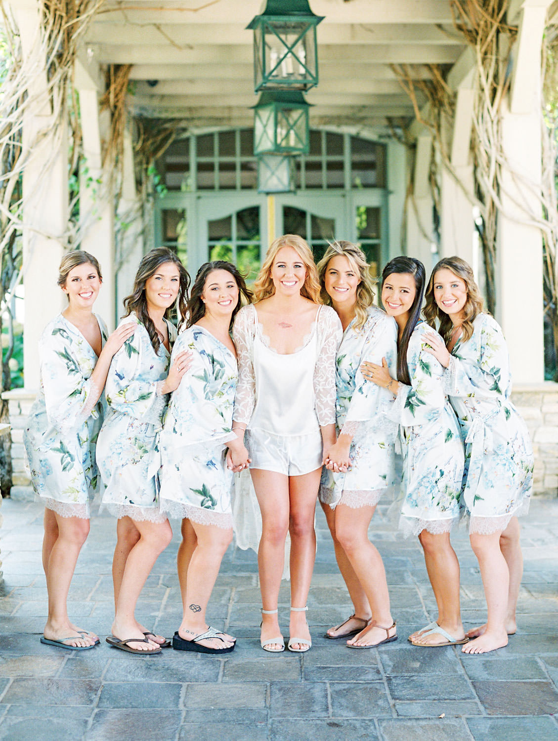 Bride in white pajamas with brides in floral robes posing before the wedding shot on film, Del Mar Country Club Wedding by Cavin Elizabeth Photography