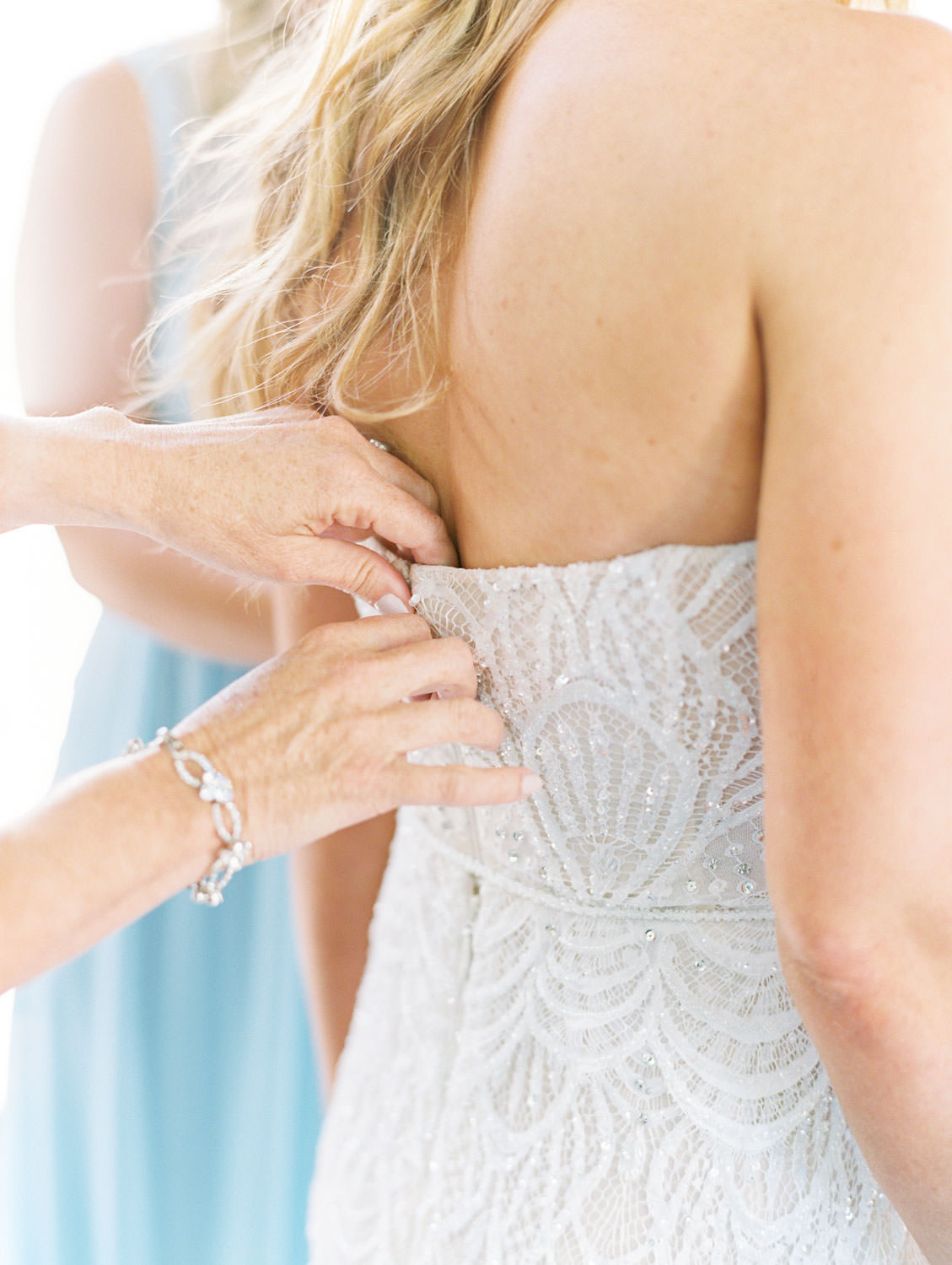 Bride getting into gown with help from sister, mom, and maid of honor wearing pale blue gowns shot on film, Del Mar Country Club Wedding by Cavin Elizabeth Photography