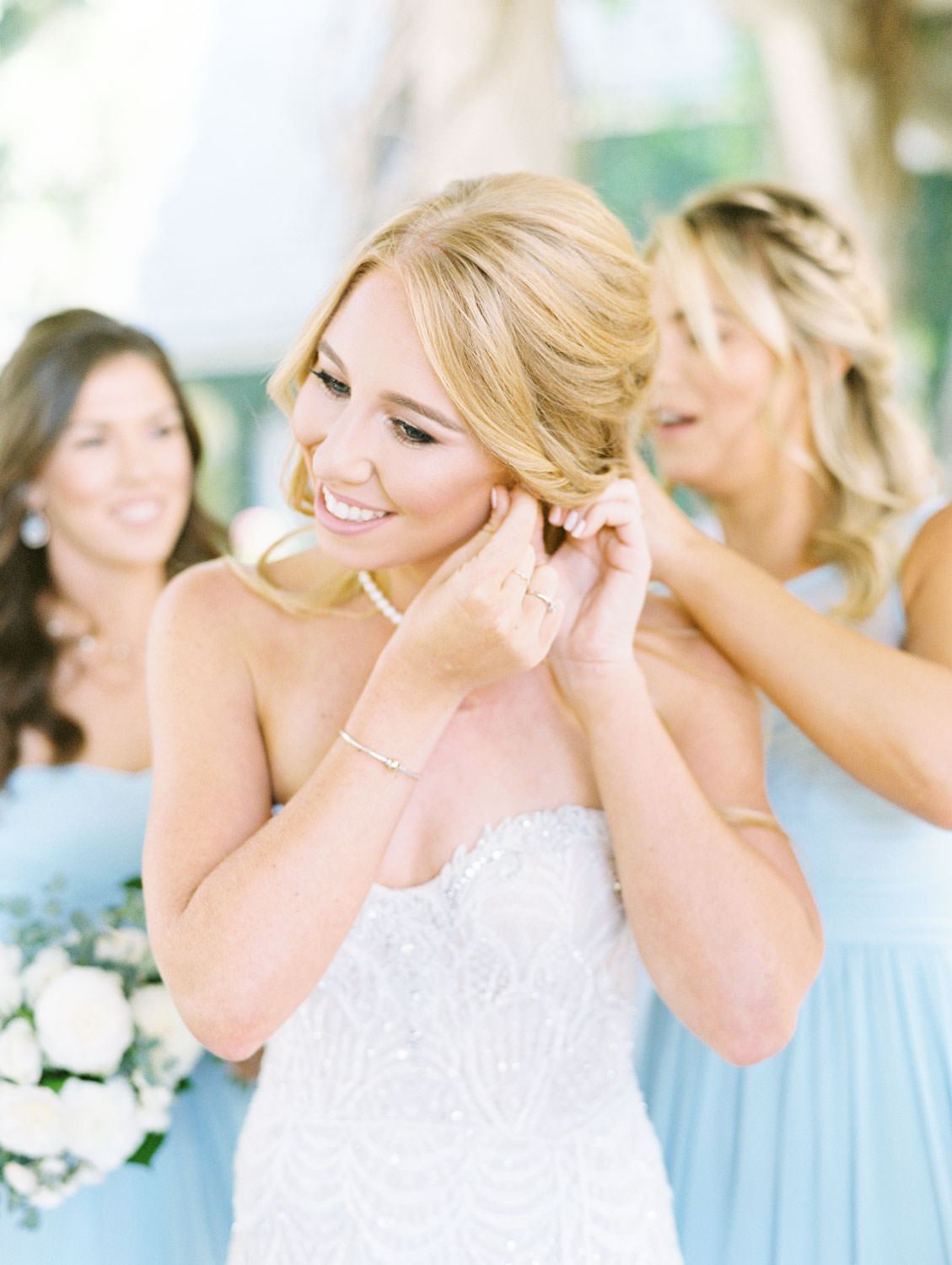Bride putting on earrings surrounded by bridesmaids wearing pale blue gowns shot on film, Del Mar Country Club Wedding by Cavin Elizabeth Photography