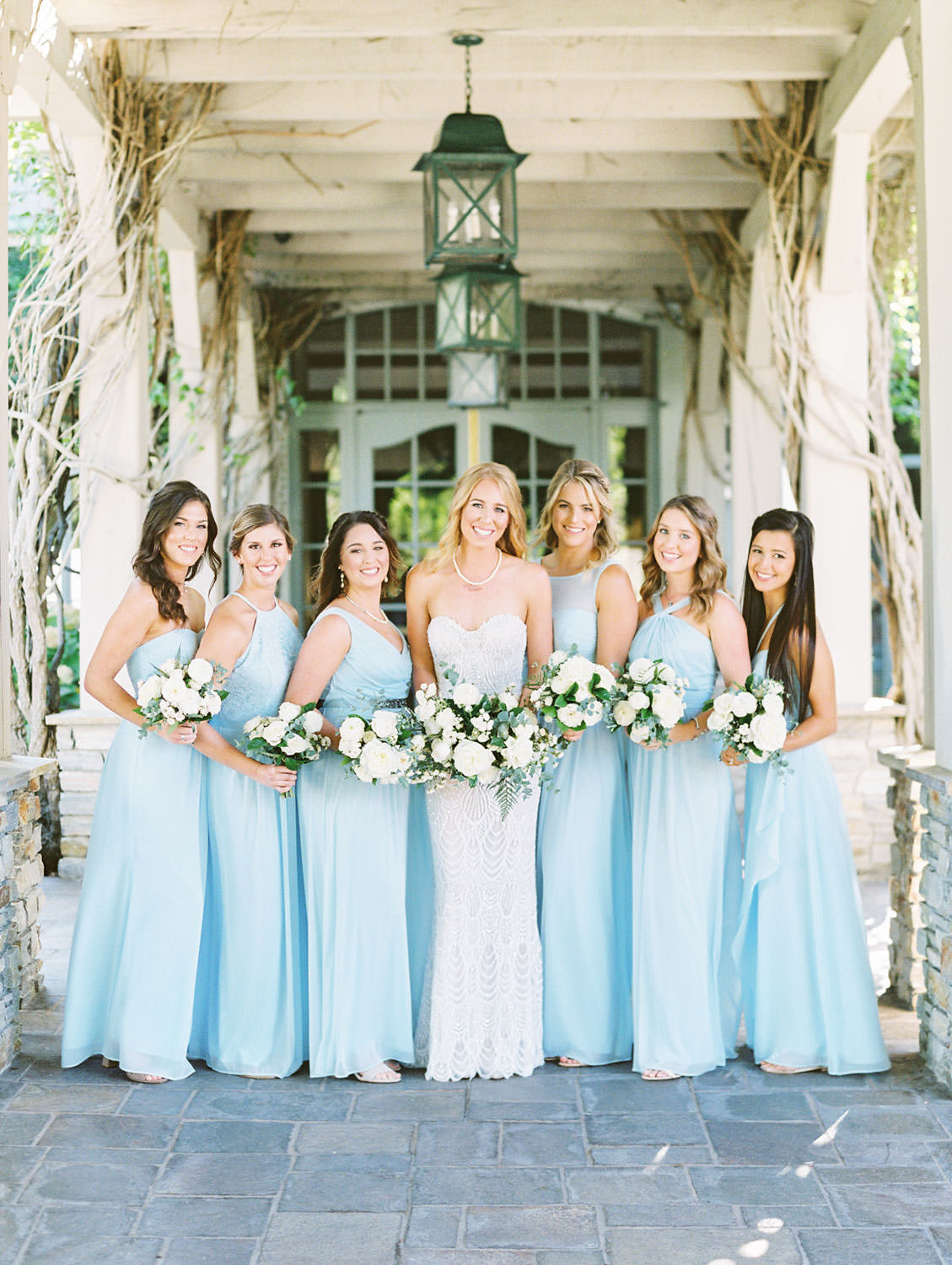 Bride with green and ivory bouquet surrounded by bridesmaids wearing pale blue gowns shot on film, Del Mar Country Club Wedding by Cavin Elizabeth Photography