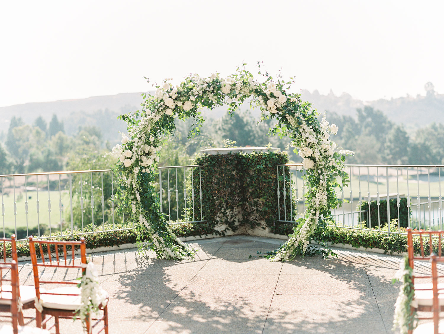Film photo of brown chiavari chairs with white cushions leading up to a semicircle arch covered in greenery and ivory flowers. Luxury wedding ceremony arch by Compass Floral, Del Mar Country Club Wedding by Cavin Elizabeth Photography