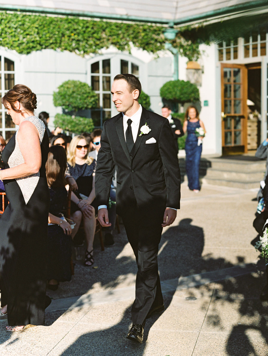 Film photo of groom walking down the aisle for his ceremony on an outdoor patio, Del Mar Country Club Wedding by Cavin Elizabeth Photography