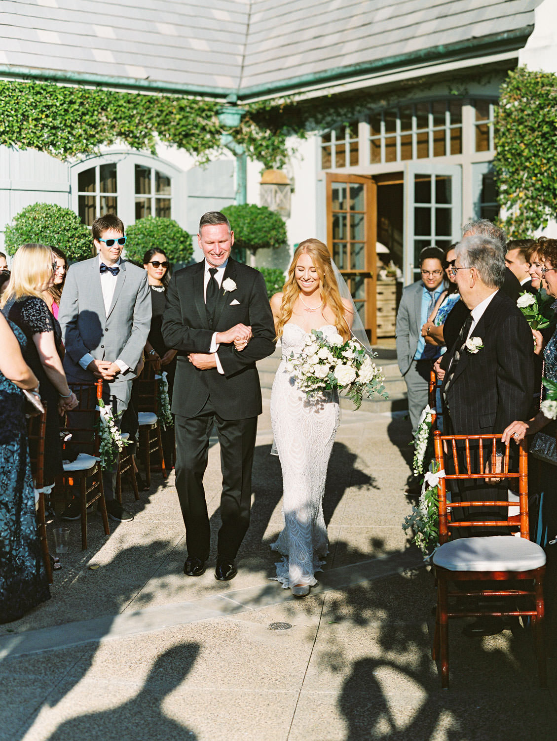 Film photo of bride and father walking down the aisle for his ceremony on an outdoor patio, Del Mar Country Club Wedding by Cavin Elizabeth Photography