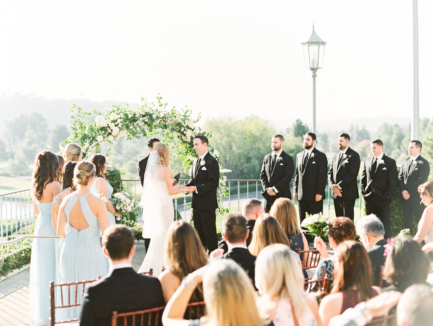 Film photo of ceremony on an outdoor patio with brown chiavari chairs and white cushions leading up to a semicircle arch covered in greenery and ivory flowers. Luxury wedding ceremony arch by Compass Floral, Del Mar Country Club Wedding by Cavin Elizabeth Photography