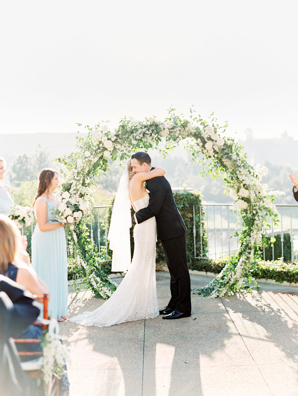 Film photo of ceremony on an outdoor patio with semicircle arch covered in greenery and ivory flowers. Luxury wedding ceremony arch by Compass Floral, Del Mar Country Club Wedding by Cavin Elizabeth Photography