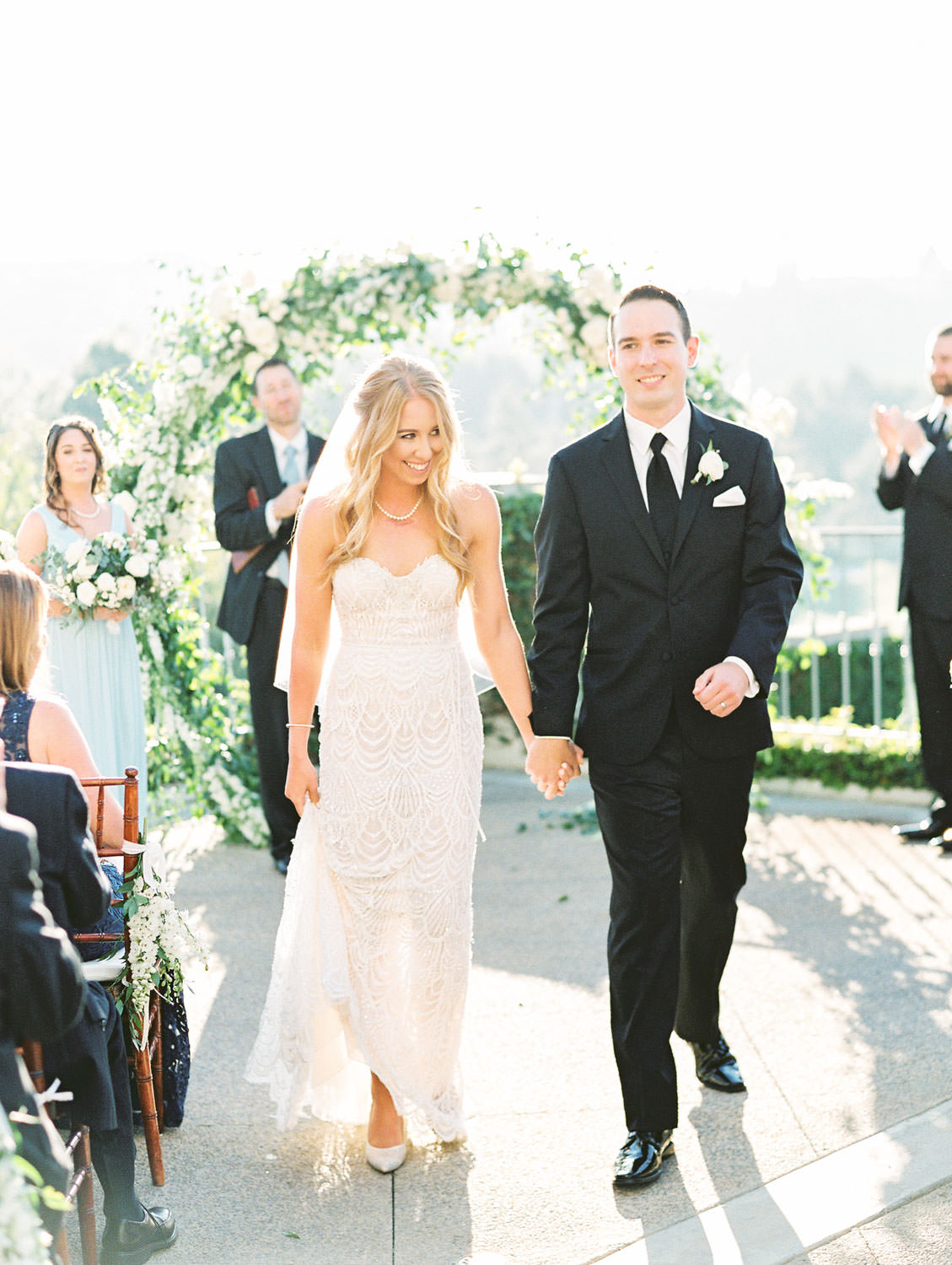 Film photo of just married bride and groom walking down the aisle away from a semicircle arch covered in greenery and ivory flowers. Luxury wedding ceremony arch by Compass Floral, Del Mar Country Club Wedding by Cavin Elizabeth Photography