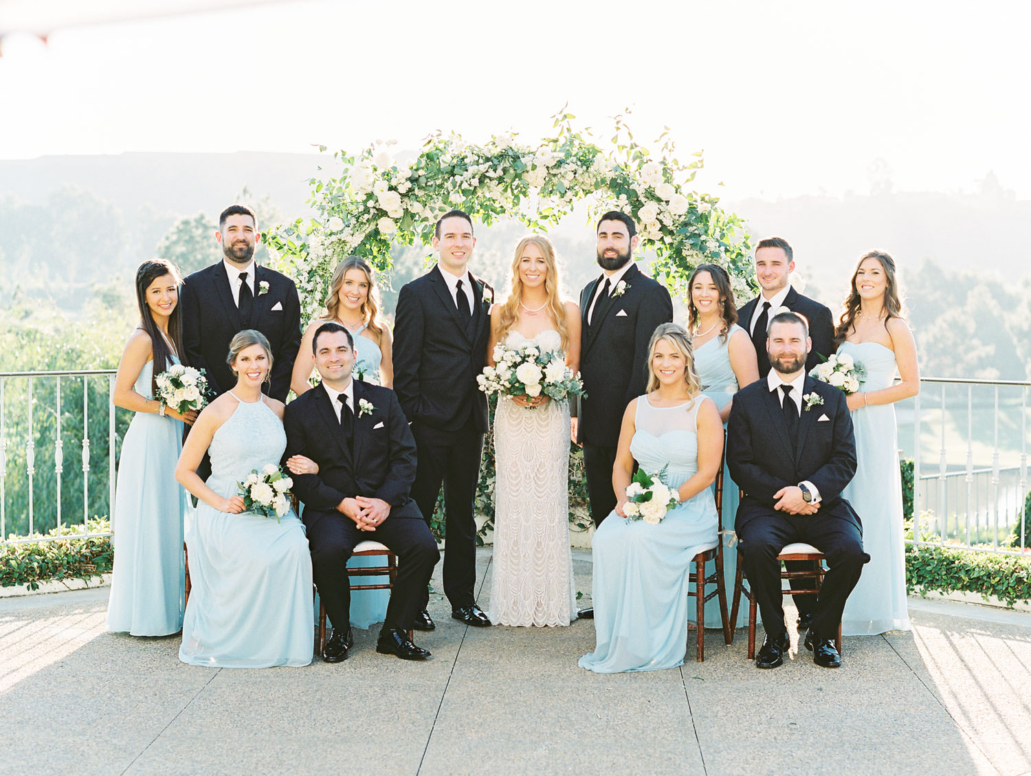 Film photo of bridal party in front of a semicircle arch covered in greenery and ivory flowers. Pale blue turquoise bridesmaids gowns and Galia Lahav bridal gown. Luxury wedding ceremony arch by Compass Floral, Del Mar Country Club Wedding by Cavin Elizabeth Photography