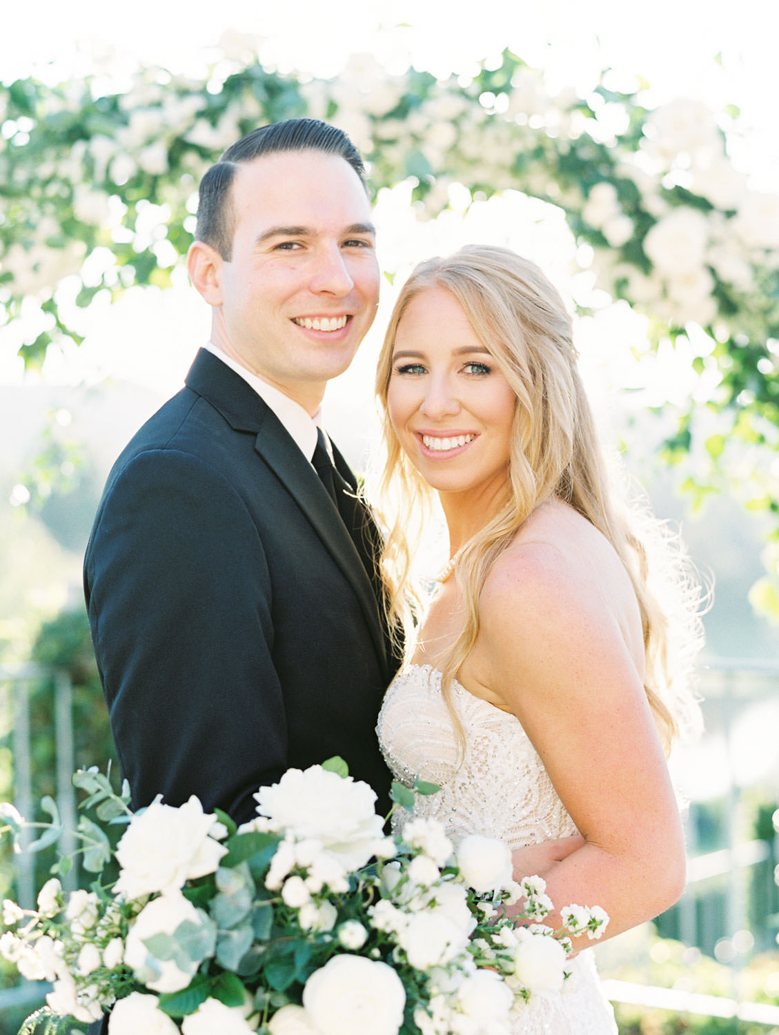 Film photo of bride and groom in front of a semicircle arch covered in greenery and ivory flowers. Luxury wedding ceremony arch by Compass Floral, Del Mar Country Club Wedding by Cavin Elizabeth Photography