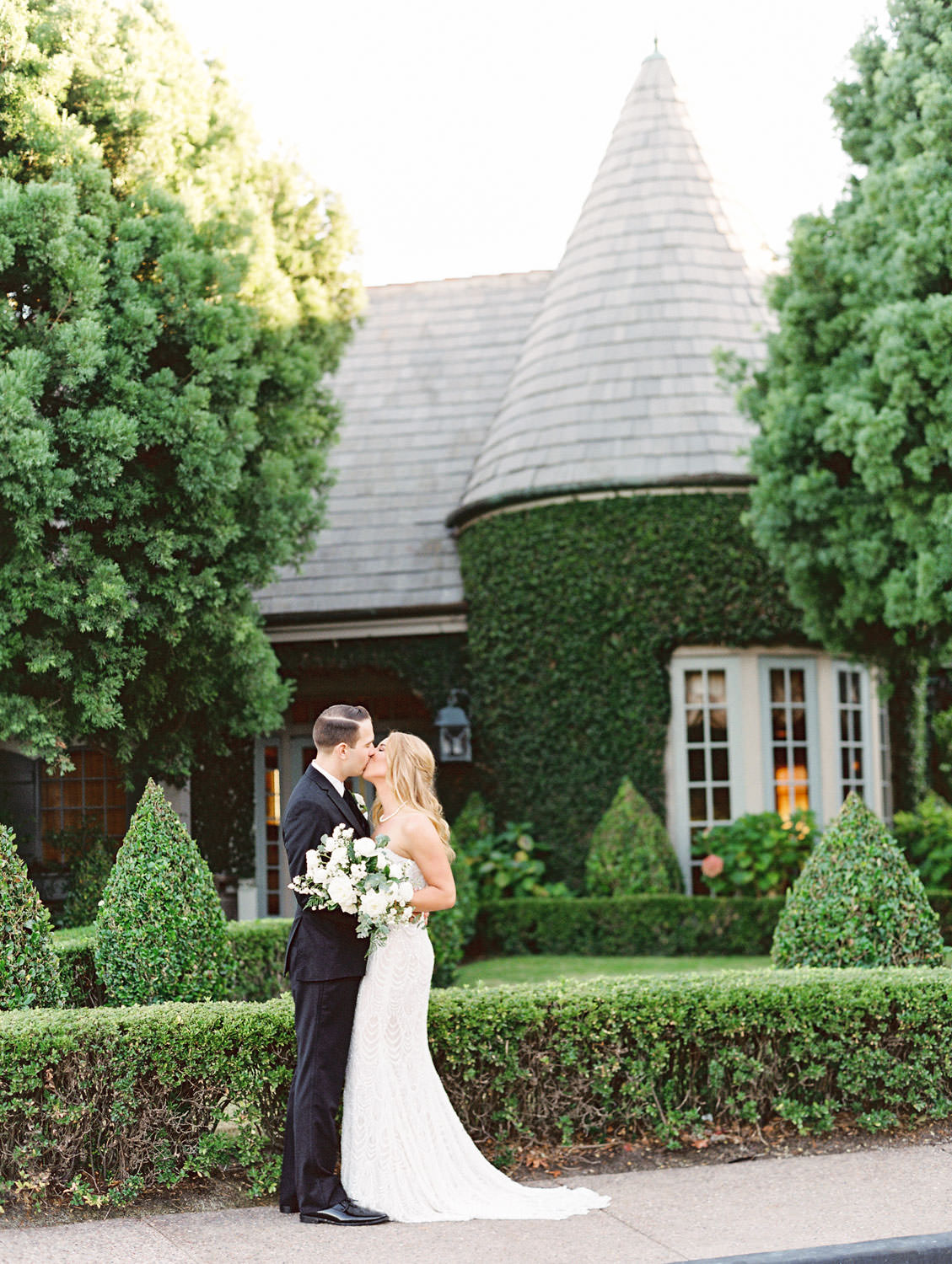 Film photo of bride and groom in front of an ivy-covered building with a turret. Bride wearing a Galia Lahav Gala gown with a sweetheart neckline carrying an ivory and green bouquet. Del Mar Country Club Wedding by Cavin Elizabeth Photography